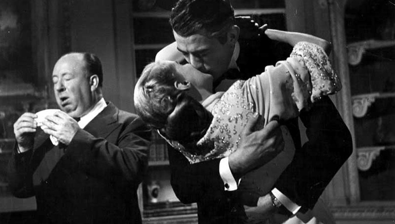 Alfred Hitchcock sneezing while Ann Todd and Gregory Peck kiss on the set of The Paradine Case